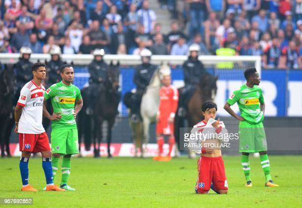Players of Moenchengladbach and Hamburg wait as mounted police stands on the pitch after Hamburg supporters throw fireworks during the German first...