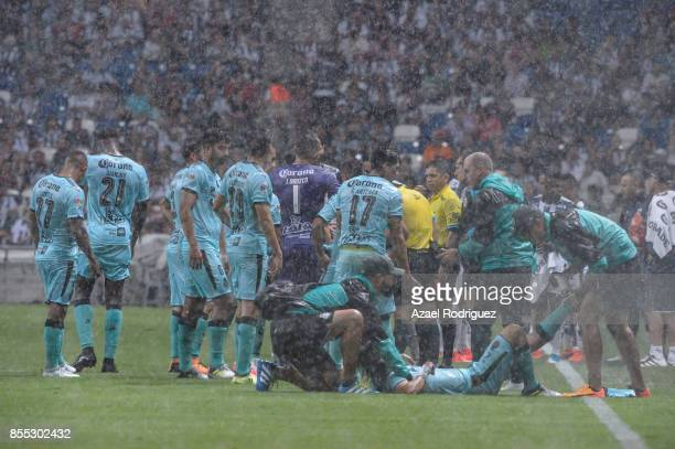 Players of Monterrey and Santos gather on the field to discuss the posible suspension of the match due to bad weather during the 11th round match...