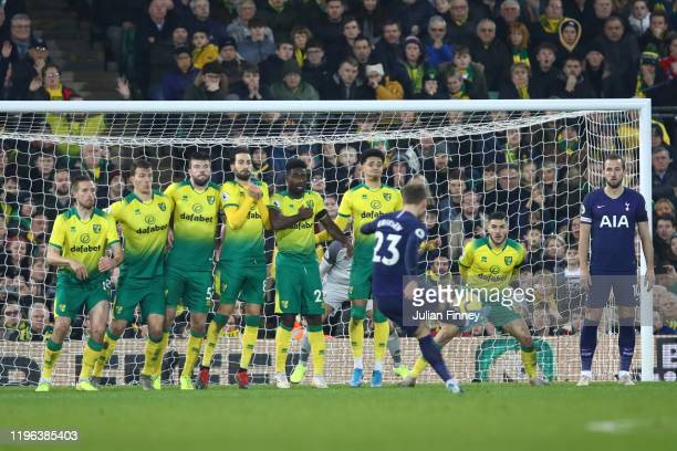 Players of Norwich City watch Christian Eriksen of Tottenham Hotspur score his team's first goal from a free-kick during the Premier League match...