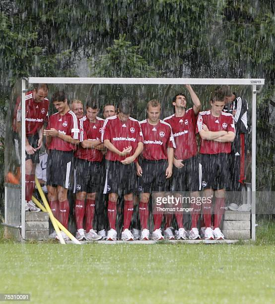 Players of Nuremberg take shelter from heavy rain and hail in a hut prior to the 1st Bundesliga Team Presentation of 1FC Nuremberg on July 10 2007 in...