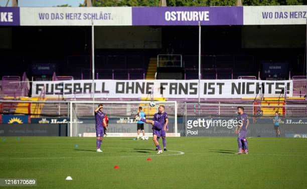 Players of Osnabrueck warm up in front of a banner reading 'Football without Fans is nothing!' prior to the Second Bundesliga match between VfL...