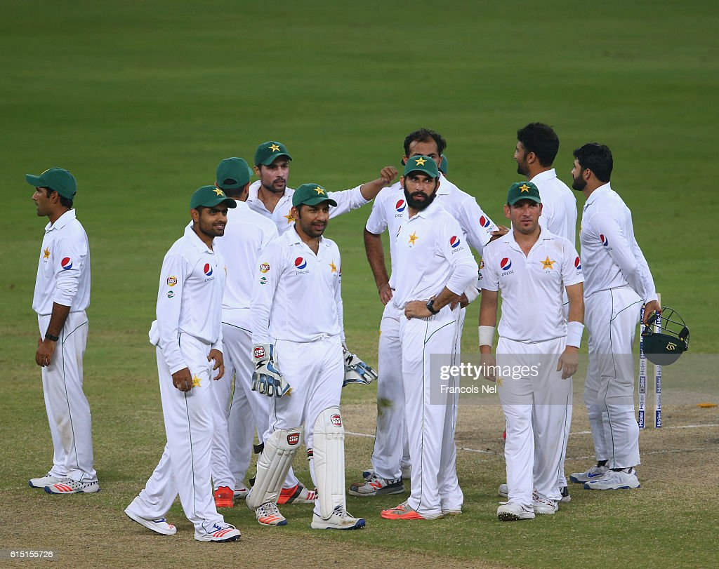 Players of Pakistan wait for a pending decision during Day