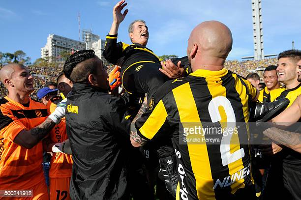 Players of Pen–arol celebrate with the assistant coach Modesto Turrens after winning a match between Penarol and Juventud as part of Torneo Apertura...