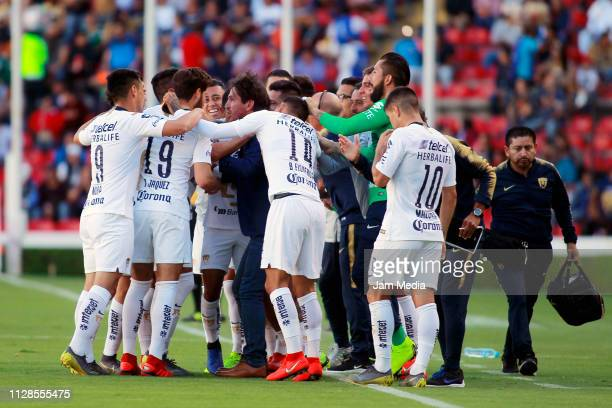 Players of Pumas celebrate their first goal with coach Bruno Marioni during the 6th round match between Queretaro and Leon as part of the Torneo...