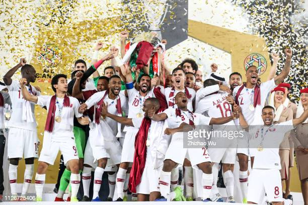 Players of Qatar celebrate their victory with the trophy after the AFC Asian Cup final match between Japan and Qatar at Zayed Sports City Stadium on...