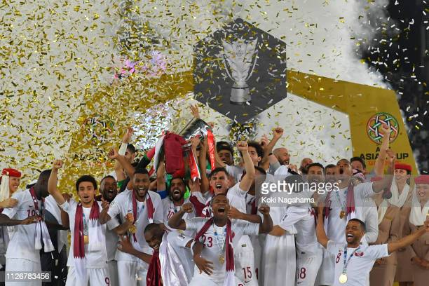 Players of Qatar celebrates their victory as Hasan Al Haydos lifts the trophy after the AFC Asian Cup final match between Japan and Qatar at Zayed...