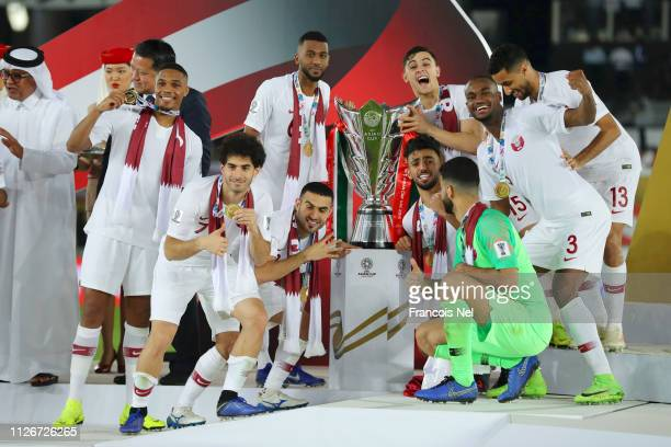 Players of Qatar pose with the AFC Asian Cup Trophy following their sides victory in the AFC Asian Cup final match between Japan and Qatar at Zayed...