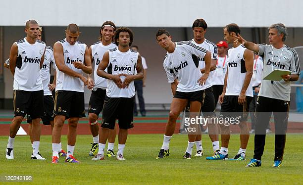 Players of Real Madrid listen to coach Jose Mourinho during a training session at Tianhe Sports Center on August 1, 2011 in Guangzhou, China.