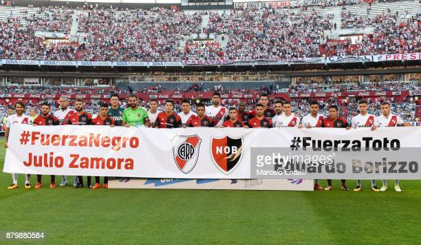 Players of River Plate and Newell's Old Boys pose with a banner in support of former players Julio Zamora and Eduardo Berizzo before a match between...