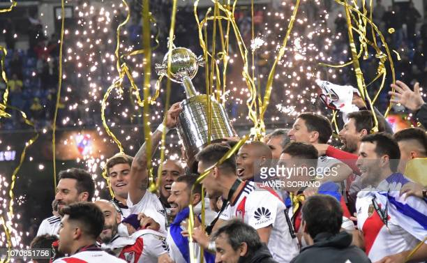 Players of River Plate celebrate with the trophy after winning the second leg match of the all-Argentine Copa Libertadores final against Boca...