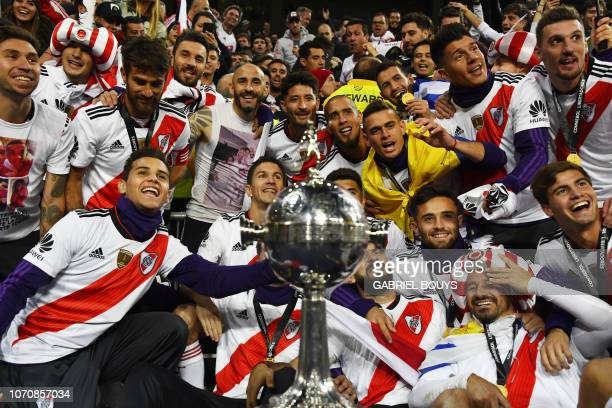 TOPSHOT Players of River Plate celebrate with the trophy after winning the second leg match of the allArgentine Copa Libertadores final against Boca...