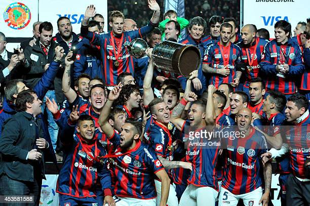 Players of San Lorenzo celebrate with the trophy after winning the second leg final match between San Lorenzo and Nacional as part of Copa...