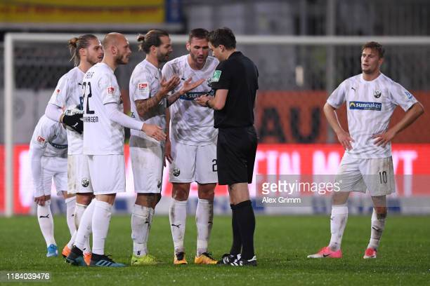 Players of Sandhausen discuss with referee Lasse Koslowski after Sandhausen's Ivan Paurevic is sent off during the Second Bundesliga match between SV...