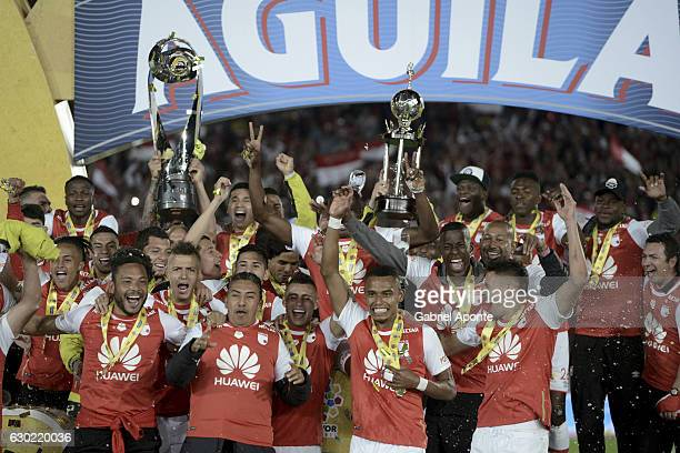 Players of Santa Fe lift the trophy after a second leg final match between Santa Fe and Deportes Tolima as part of Liga Aguila II 2016 at El Campin...