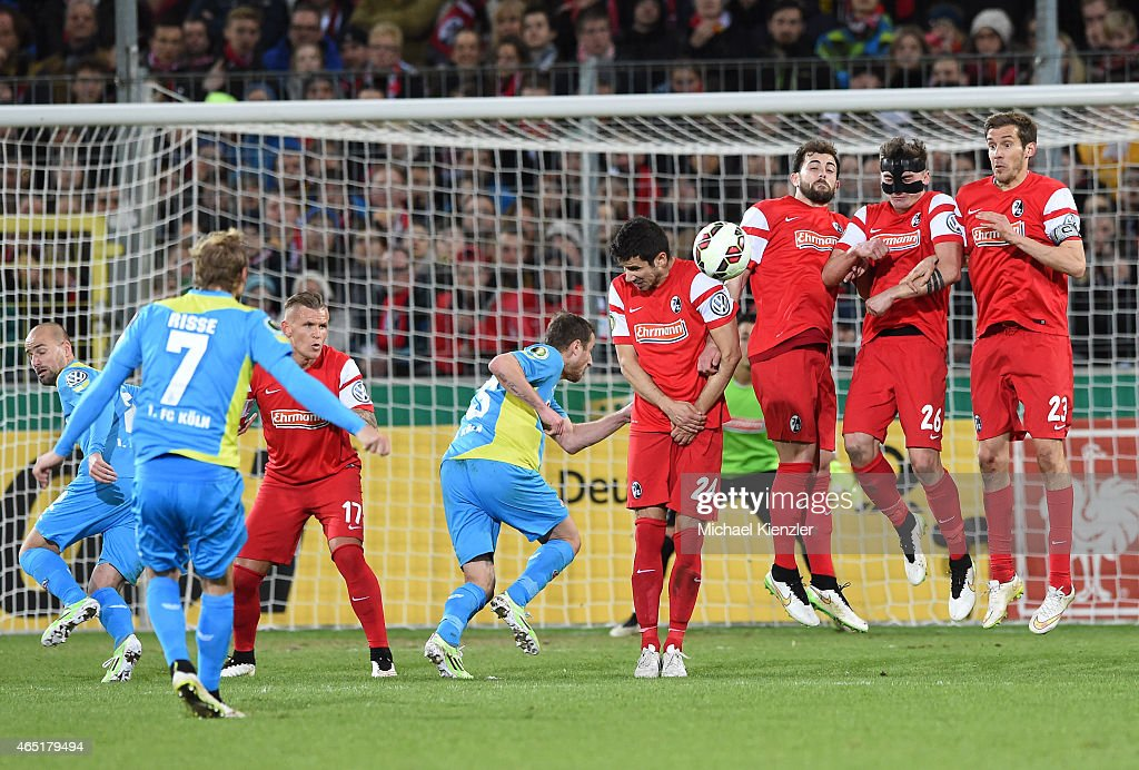 Players of SC Freiburg set up a defensive wall against the freekick of Marcel Risse of 1. FC Koeln during the DFB Cup between SC Freiburg and 1. FC Koeln at Schwarzwald-Stadium on March 3, 2015 in Freiburg, Germany.