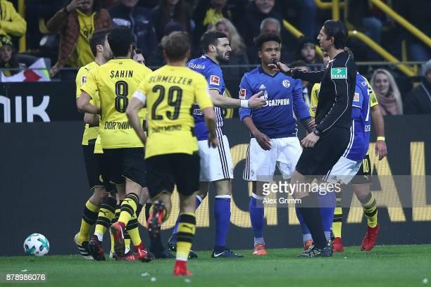 Players of Schalke and Dortmund argue with the referee Deniz Aytekin during the Bundesliga match between Borussia Dortmund and FC Schalke 04 at...