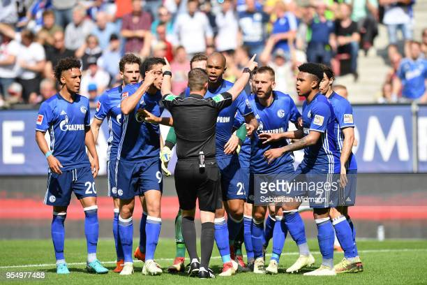 Players of Schalke argue with referee Robert Kampka during the Bundesliga match between FC Augsburg and FC Schalke 04 at WWK-Arena on May 5, 2018 in...
