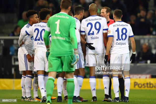 Players of Schalke surround referee Sascha Stegemann after he awarded Moechngladbach a penalty during the Bundesliga match between Borussia...