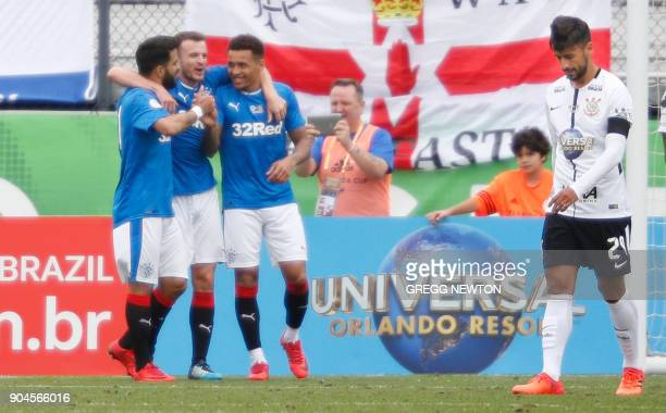 Players of Scottish club Rangers FC celebrate a second half goal while Camacho the dejected captain of Brazilian club Corinthians walks away during...