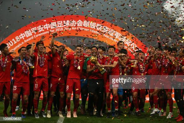 Players of Shanghai SIPG celebrate with their trophy after winning the Chinese Super League football match in Shanghai on November 7 2018 Shanghai...
