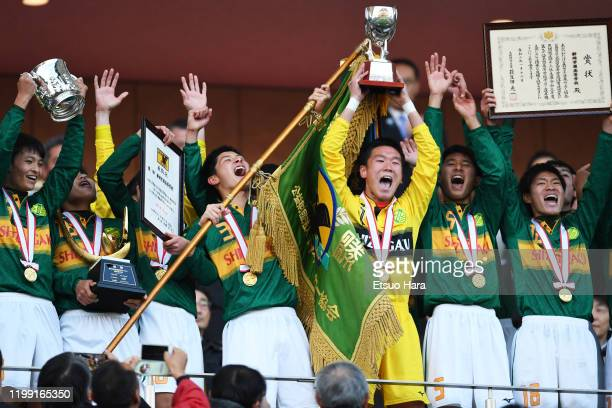 Players of Shizuoka Gakuen celebrate the victory as captain Kento Abe lifts the flag after the 98th All Japan High School Soccer Tournament final...
