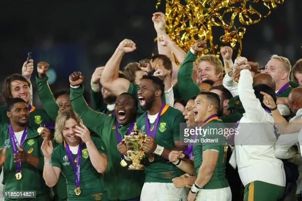 Players of South Africa celebrate as Siya Kolisi of South Africa holds the Web Ellis Cup following their victory against England in the Rugby World...