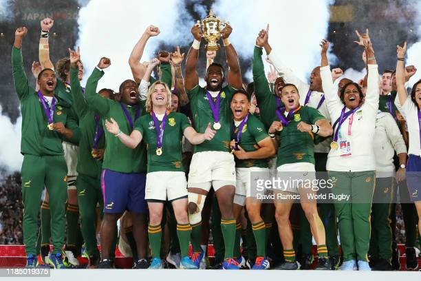 Players of South Africa celebrate as Siya Kolisi of South Africa lifts the Web Ellis Cup following their victory against England in the Rugby World...