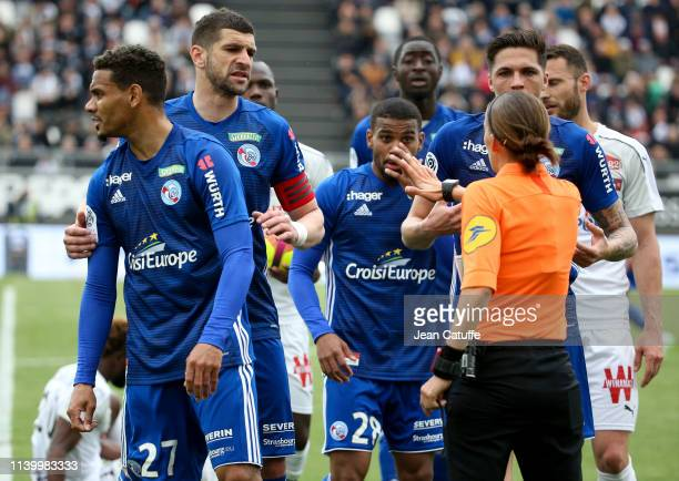 Players of Strasbourg argue with Stephanie Frappart first woman to referee a Ligue 1 match Stephanie Frappart during the French Ligue 1 match between...