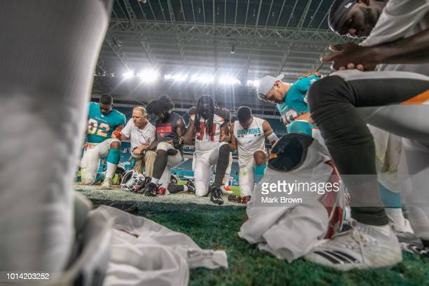 Players of Tampa Bay Buccaneers and Miami Dolphins kneel during a post game prayer at midfield after the preseason game against at Hard Rock Stadium...