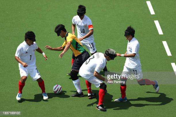 Players of Team Japan struggle to stop Tiago da Silva of Team Brazil during the 5-a-side football match between Team Brazil and Team Japan at the...