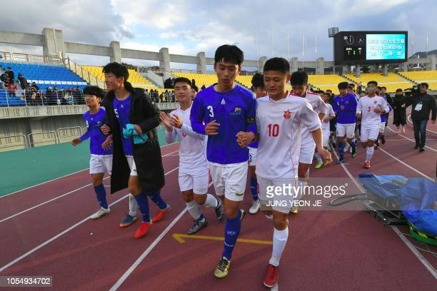 Players of the April 25 Sports Club of North Korea and the Gangwondo team of South Korea run together as they wave to their supporters after their...