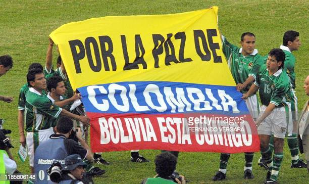 Players of the Bolivian soccer team entered the field of the Atanasio Girardot de Medellin stadium 13 July 2001 holding a flag supporting peace in...