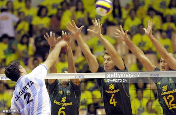 Players of the Brazilian National Volleyball Team Nalbert Andre and Mauricio try to block the ball from the Argentinian Elgueta Brasilia 28 June 2002...