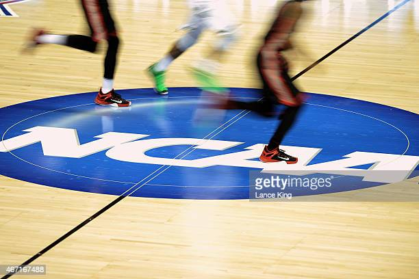 Players of the Georgia Bulldogs and Michigan State Spartans run across the NCAA logo during the second round of the 2015 NCAA Men's Basketball...