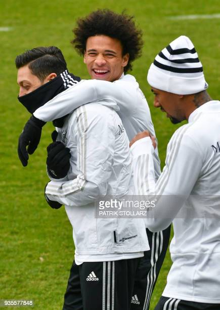 Players of the German national football team Mesut Ozil Leroy Sane and Jerome Boateng joke as they attend a training session ahead of their...