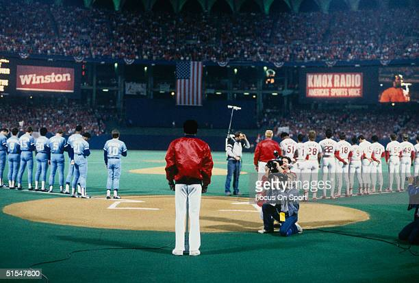 Players of the Kansas City Royals and the St Louis Cardinals stand and cover their hearts for the singing of the National Anthem during the World...