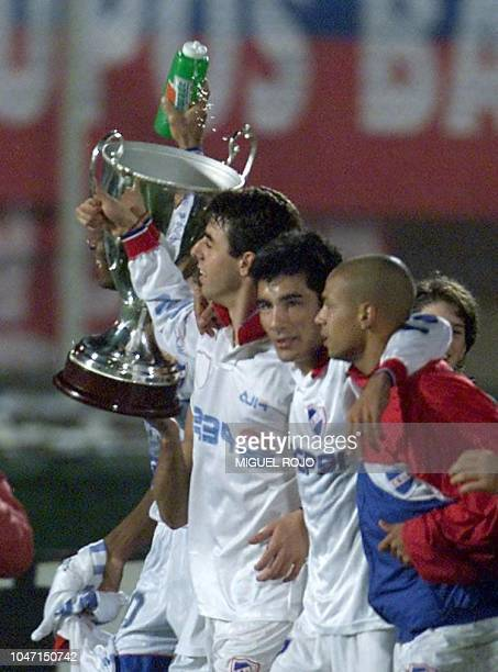 Players of the National Club of Soccer Lembo Cohelo and Varela raise the trophy of the opening match 11 June 2000 in Montevideo Los jugadores del...