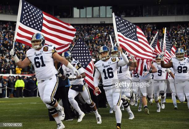 TOPSHOT Players of the Navy Midshipmen of the US Naval Academy arrive waving the American flag prior to the annual ArmyNavy football game at Lincoln...