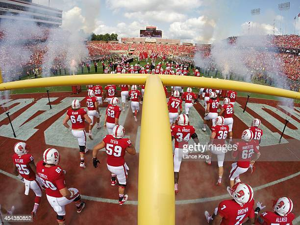 Players of the North Carolina State Wolfpack run onto the field prior to their game against the Georgia Southern Eagles at CarterFinley Stadium on...