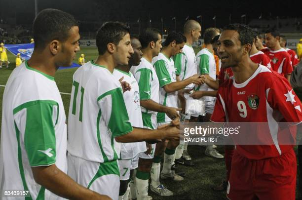 Players of the Palestinian national football team greet Jordanian players before the start of their friendly football match at the newly established...