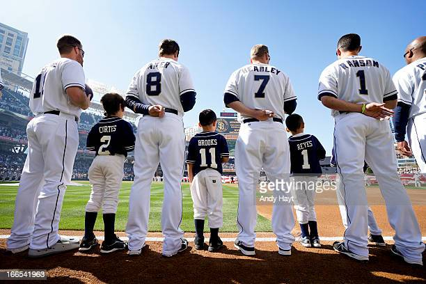 Players of the San Diego Padres stand with Little League players on the field during the pre game line up on Opening Day against the Los Angeles...
