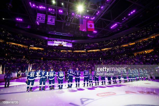 Players of the Tampa Bay Lightning line up to honor cancer heroes during Hockey Fights Cancer Night and the National Anthems as fans light up their...