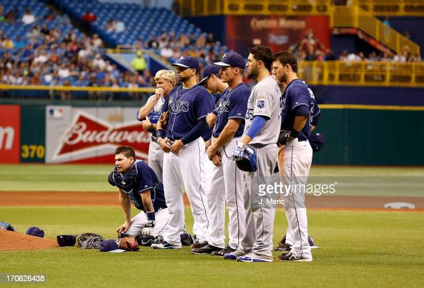 Players of the Tampa Bay Rays watch as pitcher Alex Cobb is attended to after he was hit by a line drive against the Kansas City Royals during the...