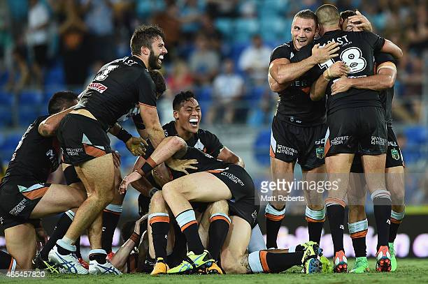 Players of the Tigers celebrate victory after a field goal by Pat Richards of the Tigers during the round one NRL match between the Gold Coast Titans...