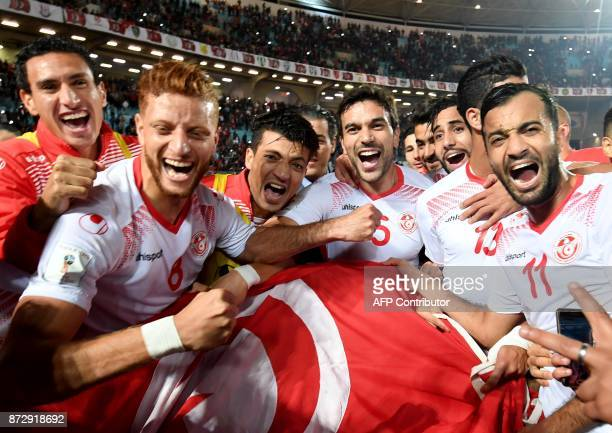 Players of the Tunisian national football team celebrate with their national flag after qualifying for the 2018 World Cup finals after drawing their...