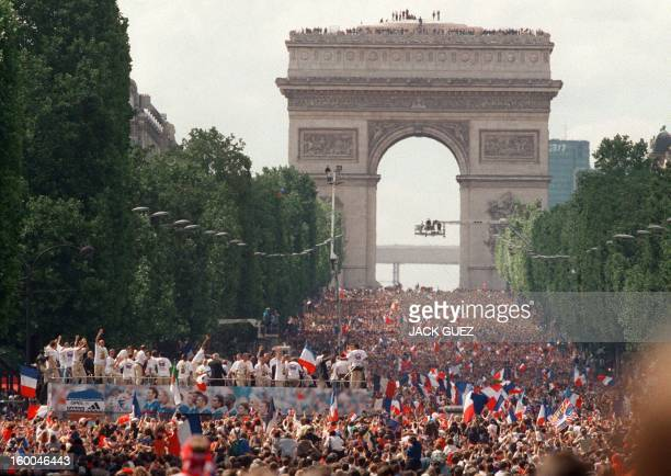 Players of the victorious French national soccer team wave to supporters during a parade on Champs Elysees avenue in Paris where hundreds of...