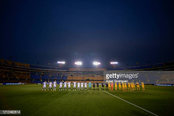 Players of Tigres and Juárez line up in an empty stadium as a measure against covid19 prior the 10th round match between Tigres UANL and FC Juarez as...