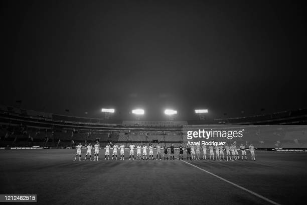 Players of Tigres and Juárez line up in an empty stadium prior to the 10th round match between Tigres UANL and FC Juarez as part of the Torneo...
