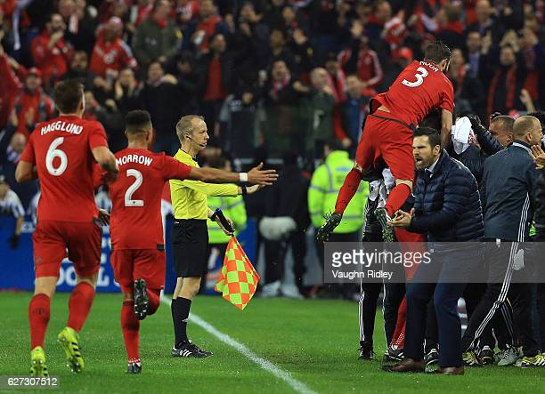 Players of Toronto FC celebrate a goal by Jozy Altidore as Head Coach Greg Vanney applauds during the first half of the MLS Eastern Conference Final...