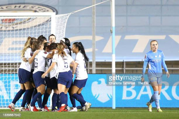 Players of Tottenham Hotspur celebrate their side's second goal, an own goal by Karima Benameur Taieb of Manchester City as Alex Greenwood of...